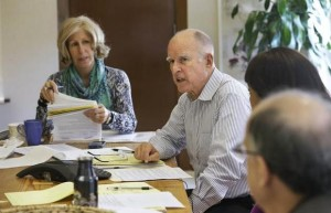 Gov. Jerry Brown discusses a bill while meeting with advisers at his Capitol office on Monday, Sept. 29, 2014 in Sacramento, Calif. Brown has until midnight Sept. 30 to sign or veto hundreds of bills that were approved in the final weeks of the legislative session. At left is advisor Nancy McFadden. RICH PEDRONCELLI — AP